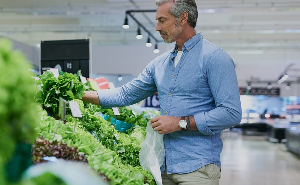 man shopping for cabbage in supermarket